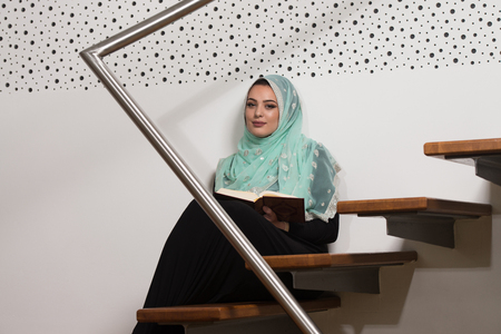 namaz: Beautiful Muslim Woman Wearing Hijab And Reading The Koran Stock Photo