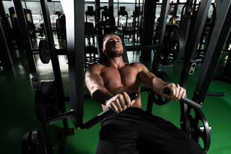 well build: Young Strong Man In The Gym And Exercising Chest On Machine - Muscular Athletic Bodybuilder Fitness Model Exercise Stock Photo