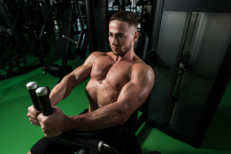 Young Bodybuilder Doing Heavy Weight Exercise For Chest On Machine Stock Photo