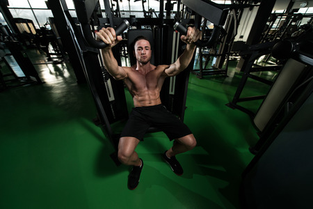 well build: Young Bodybuilder Doing Heavy Weight Exercise For Chest On Machine Stock Photo