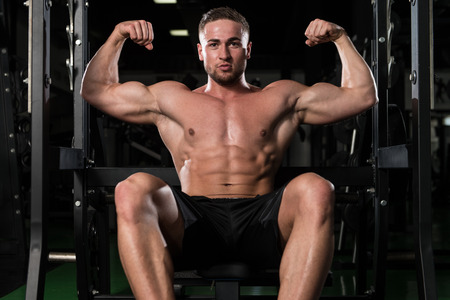 physically fit: Portrait Of A Young Physically Fit Man Performing Biceps Pose - Muscular Athletic Bodybuilder Fitness Model Posing After Exercises Stock Photo