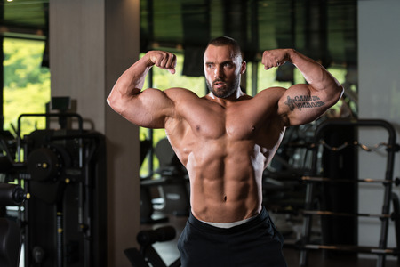 bodyart: Man Standing Strong In The Gym And Flexing Muscles - Muscular Athletic Bodybuilder Fitness Model Posing After Exercises