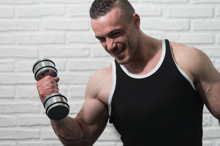 flexing: Young Man Working Out Biceps With Dumbbells On White Bricks Background With Copyspace - Dumbbell Concentration Curls