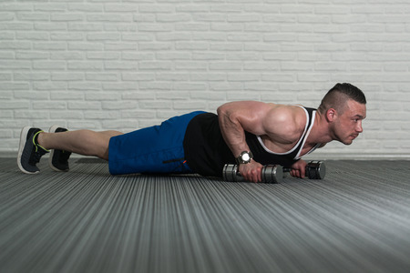 well build: Young Man Doing Pushups With Dumbbells As Part Of Bodybuilding Training