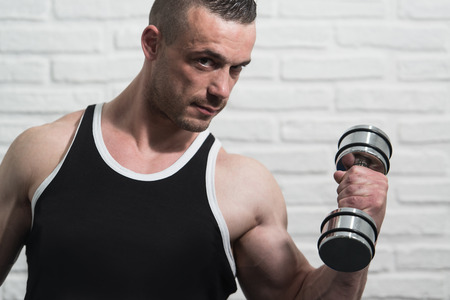 Bodybuilder Working Out Biceps With Dumbbells On White Bricks Background With Copyspace - Dumbbell Concentration Curls