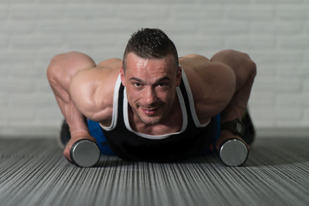 well build: Young Athlete Doing Pushups With Dumbbells As Part Of Bodybuilding Training