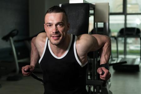 exercise machine: Young Bodybuilder Doing Heavy Weight Exercise For Triceps On Exercise Machine Stock Photo