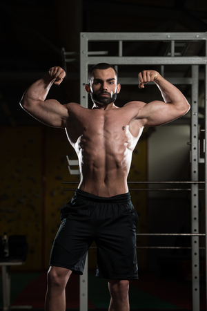 pectoral muscle: Portrait Of A Young Fit Man Showing Front Double Biceps Pose - Muscular Athletic Bodybuilder Fitness Model Posing After Exercises Stock Photo