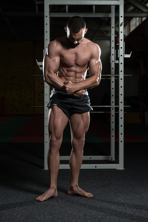 pectoral muscle: Portrait Of A Young Physically Fit Man Making Most Muscular Pose - Muscular Athletic Bodybuilder Fitness Model Posing After Exercises