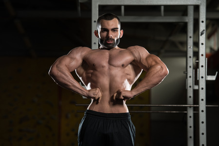 Portrait Of A Young Fit Man Performing Front Lat Spread Pose - Muscular Athletic Bodybuilder Fitness Model Posing After Exercises