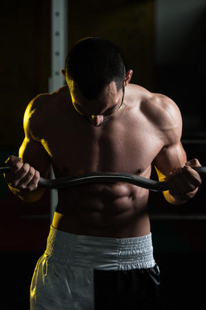 Muscular Man Doing Heavy Weight Exercise For Biceps With Barbell In Gym Stock Photo
