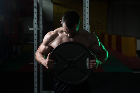 Portrait Of A Physically Young Man Holding Weights In Hand In A Dark Gym Stock Photo