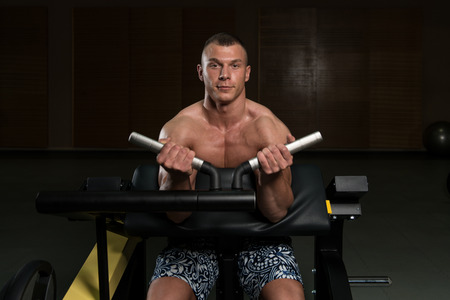well build: Young Bodybuilder Doing Heavy Weight Exercise For Biceps On Machine