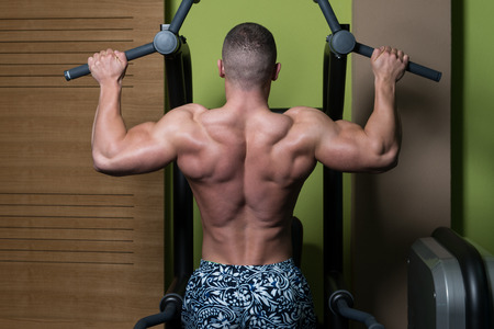 ups: Young Man Athlete Doing Pull Ups - Chin-Ups In The Gym Stock Photo