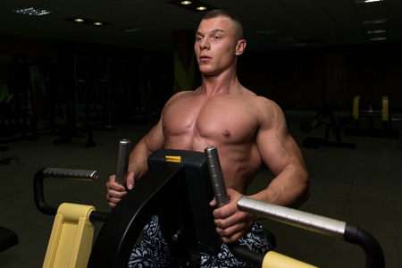 well build: Muscular Athletic Bodybuilder Fitness Model Doing Heavy Weight Exercise For Back On Machine