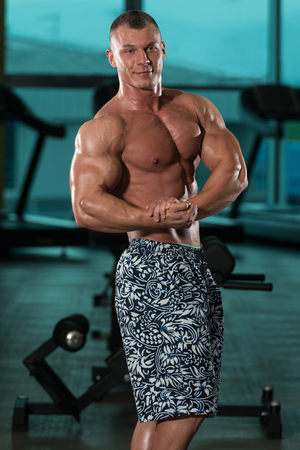 Young Man Standing Strong In The Gym And Flexing Muscles - Muscular Athletic Bodybuilder Fitness Model Posing After Exercises Stock Photo
