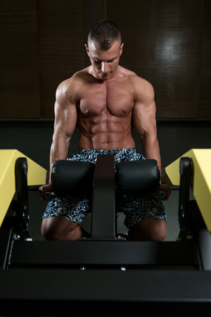trapezius: Young Bodybuilder Doing Heavy Weight Exercise For Trapezius