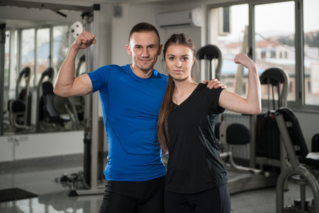 together standing: Portrait Of Fit Couple Together Standing In A Gym Looking Positive