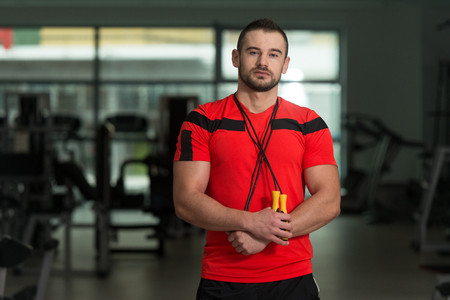Portrait Of A Physically Fit Man Personal Trainer Posing With Jumping Rope In Modern Fitness Center Gym