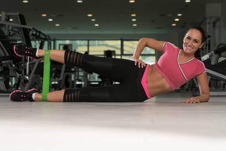 Attractive Woman Exercising With A Resistance Band On Floor In Gym As Part Of Fitness Training Stock Photo