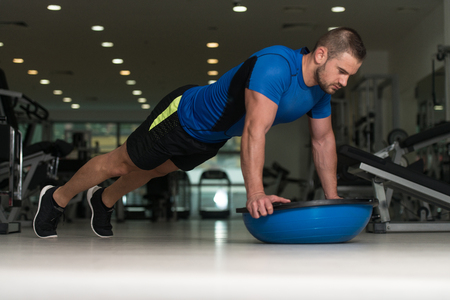 Personal Trainer Doing Pushups On Floor With Bosu Balance Ball As Part Of Bodybuilding Training