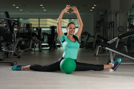 ball stretching: Attractive Woman Doing Stretching With Medicine Ball As Part Of Bodybuilding Training
