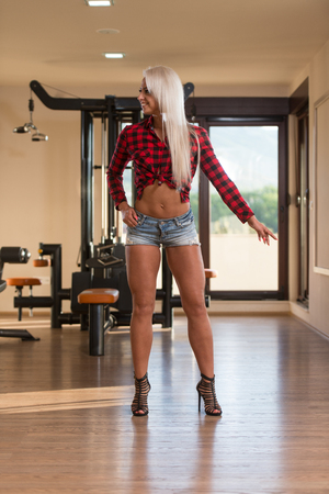plaid shirt: Young Woman Standing Strong In Plaid Shirt Flexing Muscles - Pretty Athletic Fitness Model Posing After Exercises