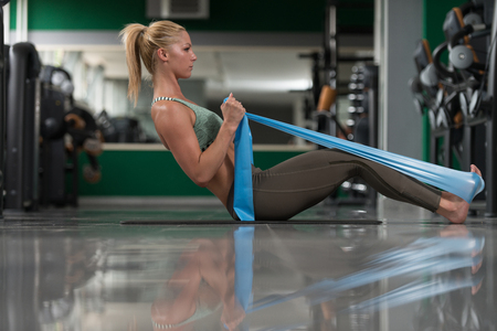 athleticism: Attractive Woman Exercising With A Resistance Band On Floor In Gym As Part Of Fitness Training Stock Photo