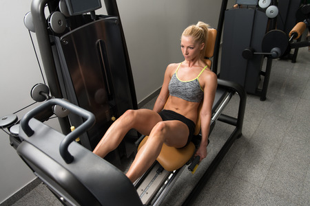 Healthy Young Woman Using The Leg Press Machine At A Health Club In Gym Stock Photo