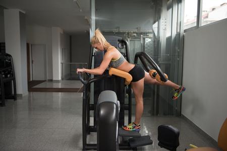 health club: Healthy Young Woman Exercise Legs On Machine At A Health Club In Gym