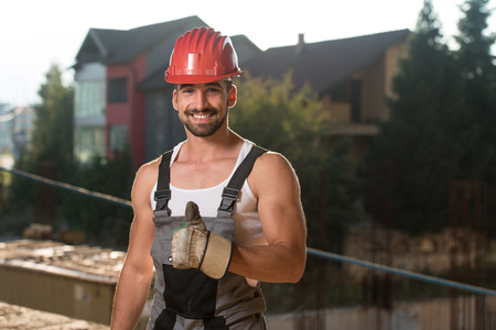 casco rojo: Portrait Of A Construction Worker With Red Helmet Making Thumbs Up Sign