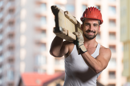 Smiling Carpenter Carrying A Large Wood Plank On His Shoulder