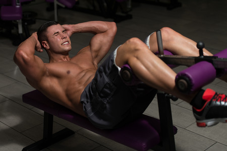 abdominals: Young Healthy Man Exercising Abdominals In Gym