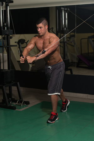 crossover: Young Man Is Working On His Chest With Cable Crossover In A Modern Fitness Gym Stock Photo