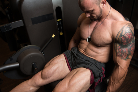 quadriceps: Attractive Man Doing Leg Exercises On Machine In Gym