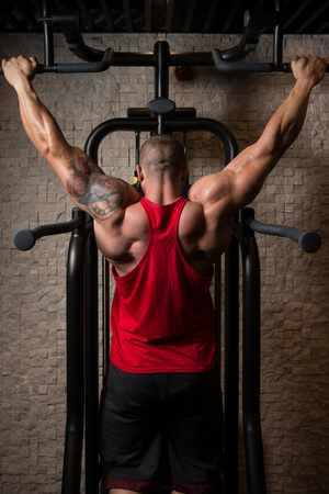 strong chin: Man Athlete Doing Pull Ups - Chin-Ups In The Gym