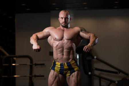 sixpack: Man Standing Strong In The Gym And Flexing Muscles - Muscular Athletic Bodybuilder Fitness Model Posing After Exercises