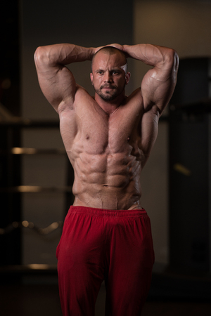 physically fit: Portrait Of A Physically Fit Man Showing His Well Trained Body - Muscular Athletic Bodybuilder Fitness Model Posing After Exercises