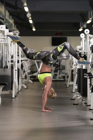 stretchy: Flexible Girl Standing On Hands And Do The Splits In Gym