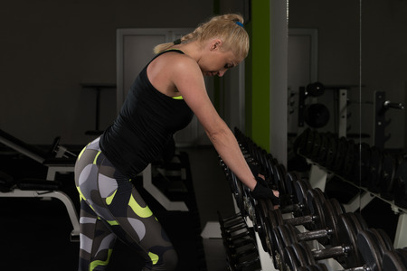 Portrait Of A Young Physically Fit Woman Relaxing In A Gym - Muscular Athletic Bodybuilder Fitness Model Resting