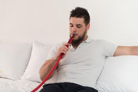 Young Man Smoking Shisha At Arabic Restaurant - Man Exhaling Smoke Inhaling From A Hookah