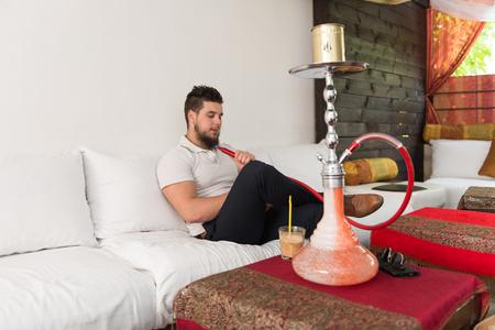 turkish ethnicity: Young Man Smoking Shisha At Arabic Restaurant - Man Exhaling Smoke Inhaling From A Hookah