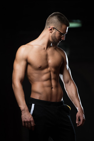 Handsome Geek Man Standing Strong In The Gym And Flexing Muscles - Muscular Athletic Bodybuilder Fitness Model Posing After Exercises