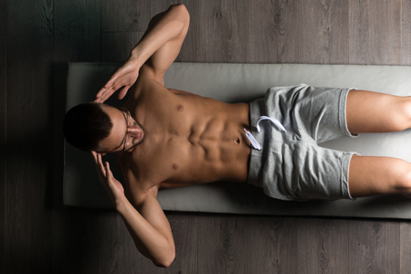 laying abs exercise: Healthy Man Exercising Abdominals On Foor