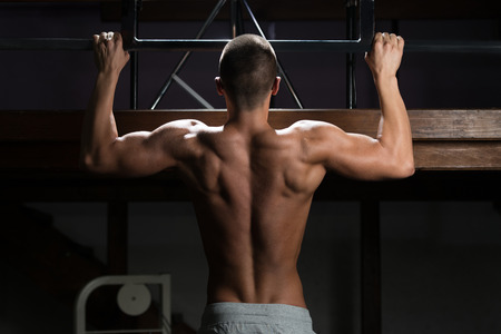 strong chin: Handsome Man Athlete Doing Pull Ups - Chin-Ups In The Gym Stock Photo