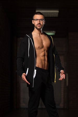 muscle training: Portrait Of A Young Physically Fit Nerd Man Showing His Well Trained Body In Sports Clothing - Muscular Athletic Bodybuilder Fitness Model Posing After Exercises Lizenzfreie Bilder