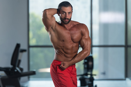 Portrait Of A Young Physically Fit Hispanic Man Showing His Well Trained Abdominal Muscles - Muscular Athletic Bodybuilder Fitness Model Posing After Exercises Stock Photo