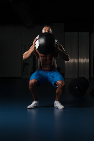 Latin Male Athlete Crouched Doing Wall Balls Exercises At The Gym