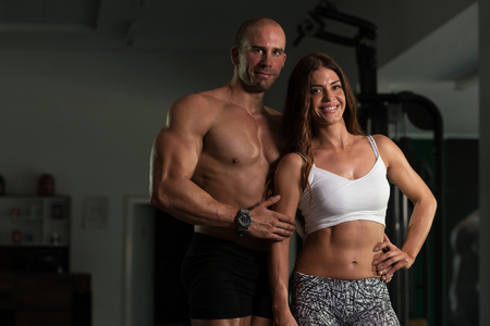 Portrait Of A Physically Fit Couple Showing Their Well Trained Body - Muscular Athletic Bodybuilder Fitness Model Posing After Exercises