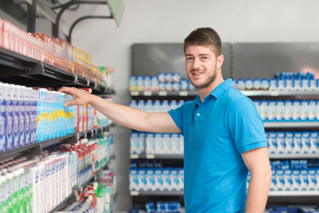 Handsome Young Man Shopping For Milk And Cheese In Produce Department Of A Grocery Store - Supermarket - Shallow Deep Of Field